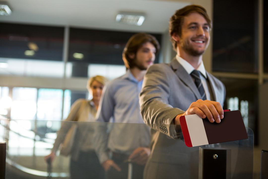 Businessman standing with boarding pass at check-in counter in airport Free Stock Images from PikWizard