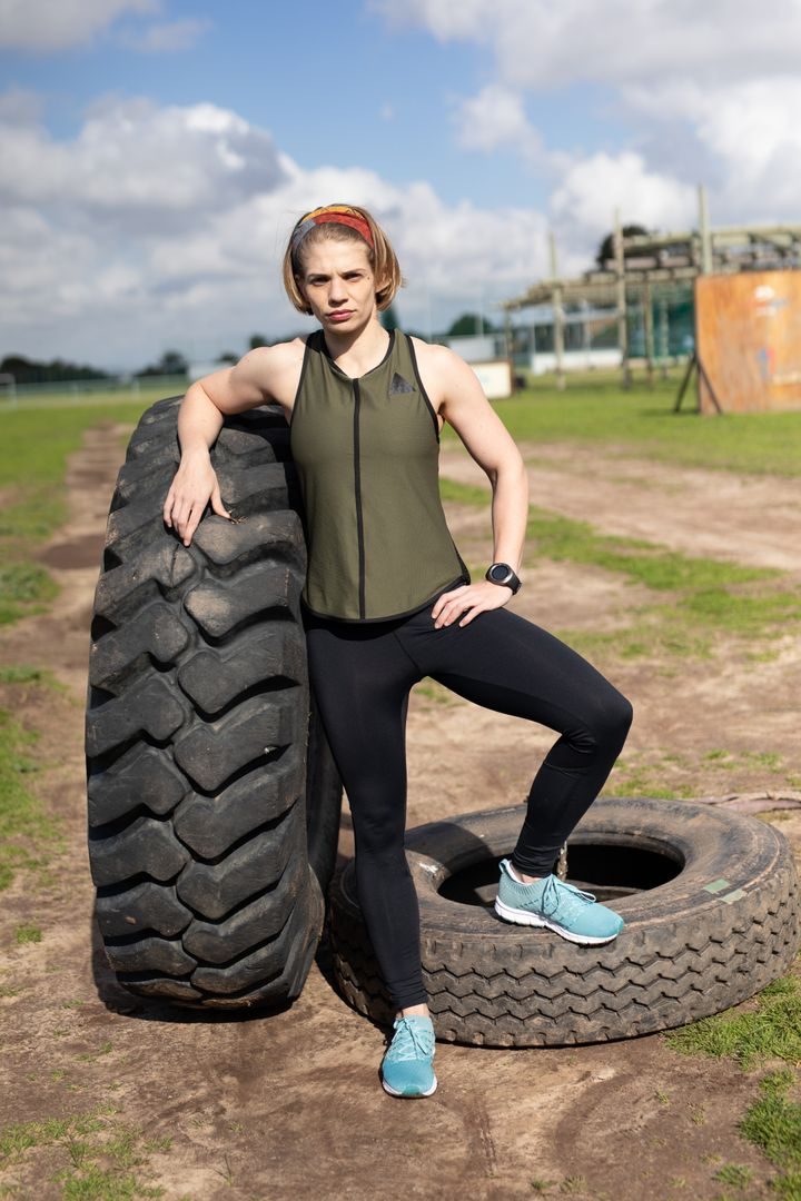Portrait of a Caucasian woman wearing sports clothes at an outdoor gym standing with one foot on a tyre and leaning on a tractor tyre, and looking to camera before a bootcamp training session Free Stock Images from PikWizard