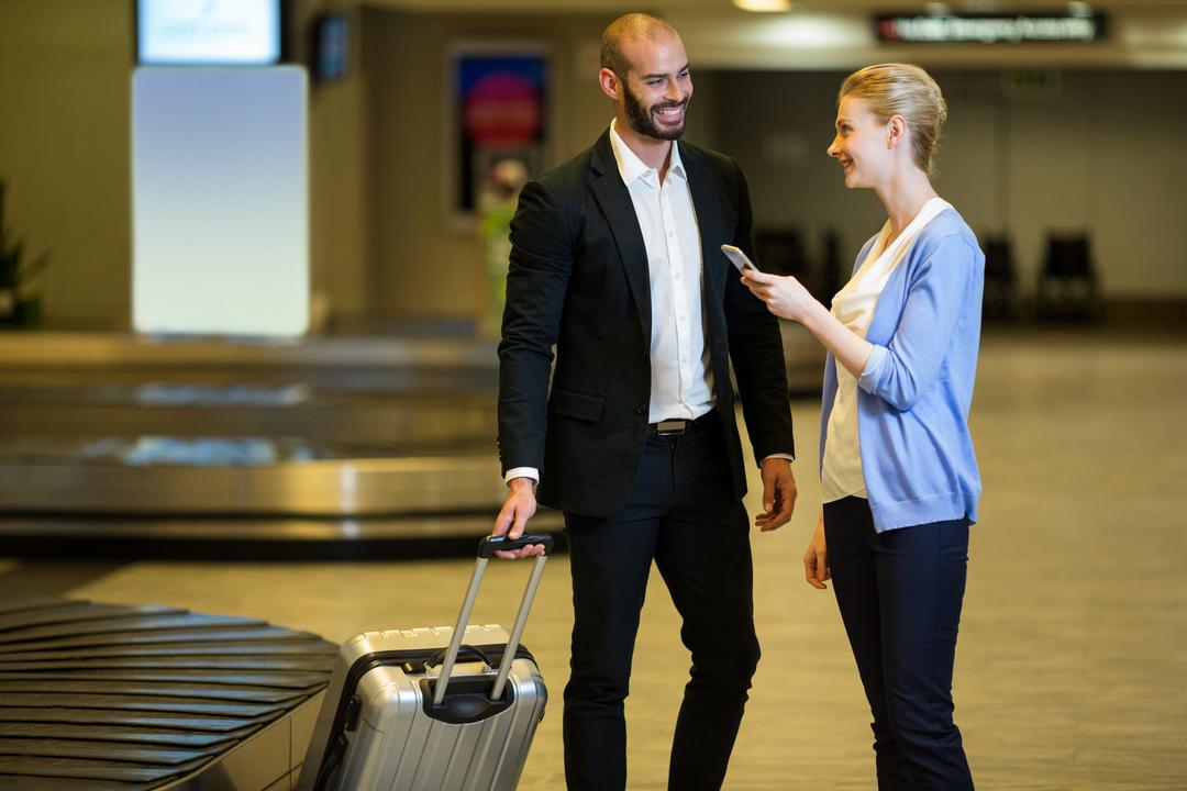 Smiling couple interacting with each other in waiting area at airport terminal
