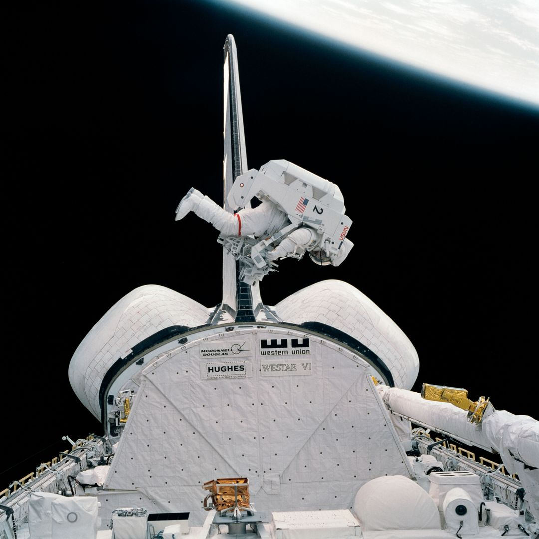 S84-27023 (7 Feb 1984) --- This 70mm frame shows astronaut Bruce McCandless II moving in to conduct a test involving the Trunion Pin Attachment Device (TPAD) he carries and the Shuttle Pallet Satellite (SPAS-01A) partially visible at bottom of frame. SPAS was a stand-in for the damaged Solar Maximum Satellite (SMS) which will be visited for repairs by the STS-41C Shuttle crew in early spring.  This particular Extravehicular Activity (EVA) session was a rehearsal for the SMS visit. The test and the actual visit to the SMS both involve the use of jet-powered, hand-controlled Manned Maneuvering Unit (MMU). The one McCandless uses is the second unit to be tested on this flight. Astronaut Robert L. Stewart got a chance to work with both MMU's on the two EVA's.