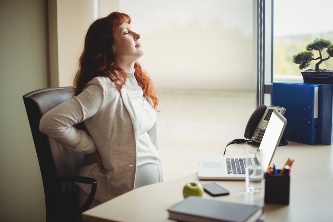 Pregnant businesswoman holding her back while sitting on chair in office