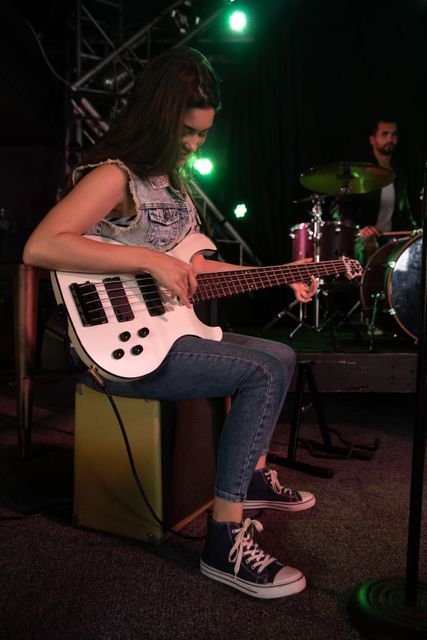 Caucasian woman sitting and playing electric guitar with male drummer and band equipment on stage at a music venue during concert in the background. Entertainment fun music.