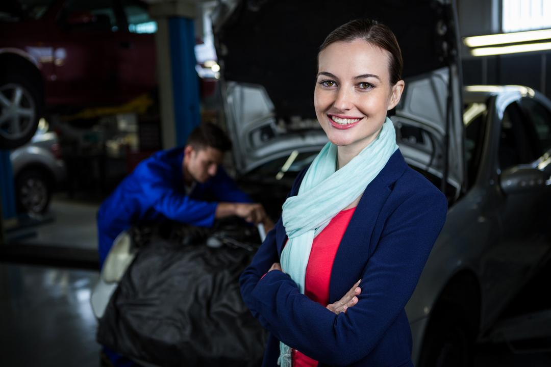 Portrait of female customer standing with arms crossed at repair garage Free Stock Images from PikWizard