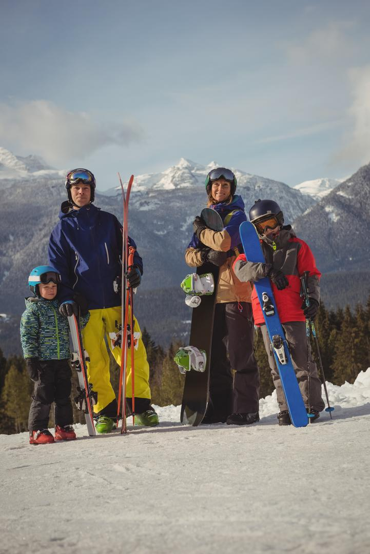 Family in skiwear standing together on snowy alps during winter