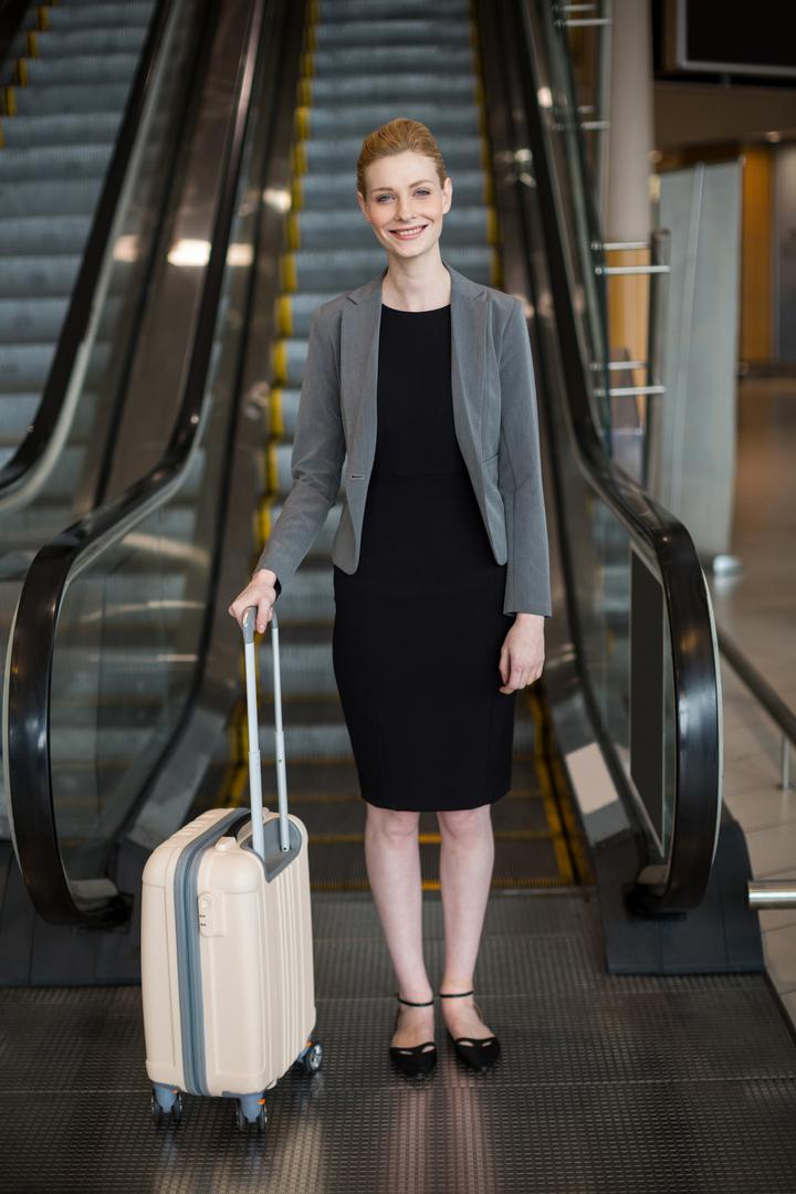 Businesswoman standing near escalator with luggage at airport Free Stock Images from PikWizard