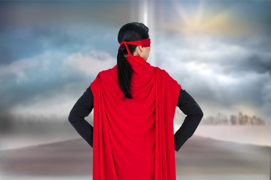 Digital composite of Rear view of business person wearing superhero cape against sky