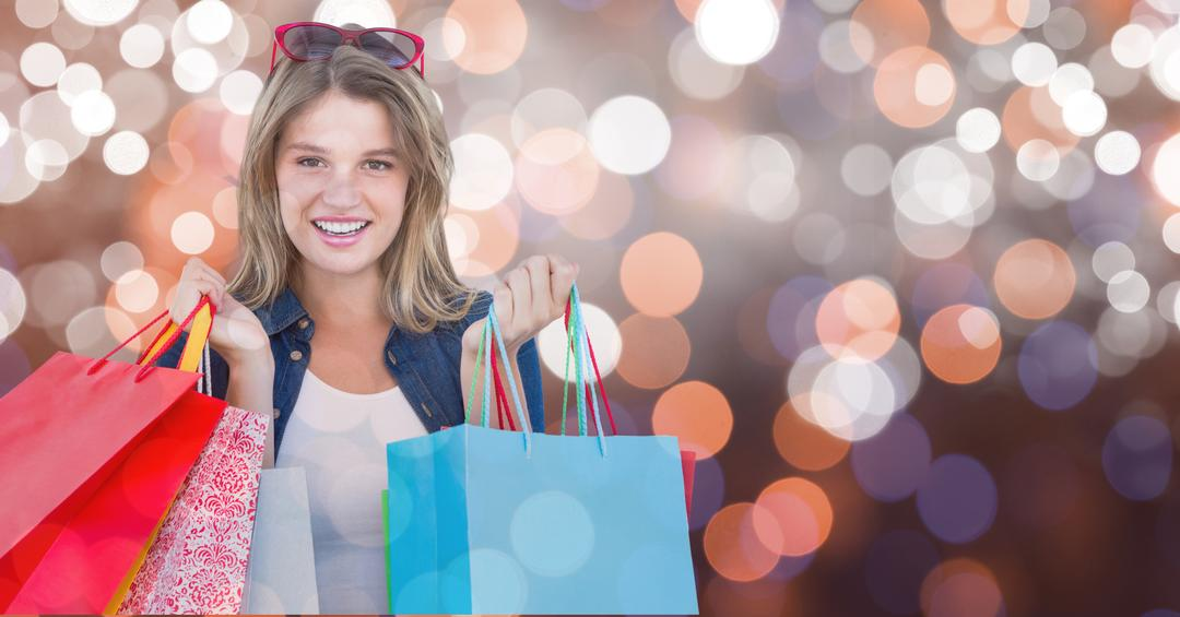 Digital composite of Portrait of woman smiling while holding shopping bags over bokeh Free Stock Images from PikWizard