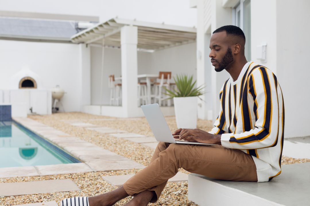 Side view of an African-American man using a laptop while sitting outdoors by the pool