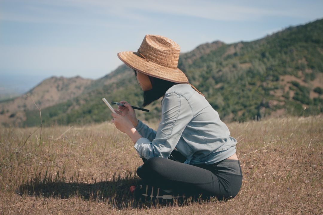 Woman sitting in the middle of a field writing in a notepad