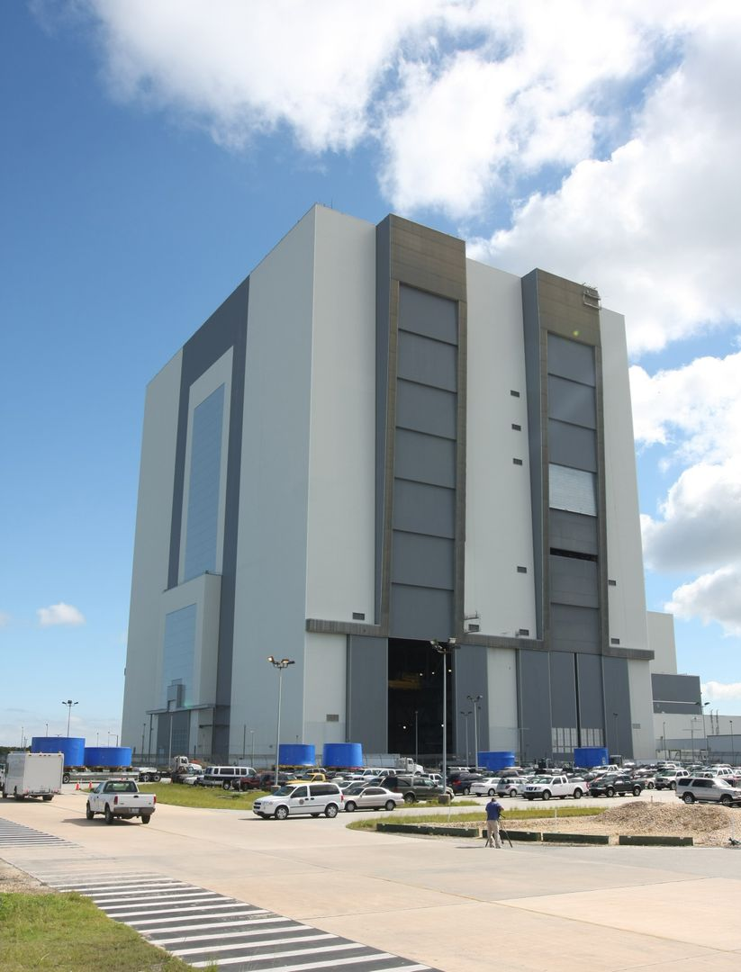 CAPE CANAVERAL, Fla. –  Trucks carrying the blue Ares I-X upper stage simulator segments are lined up outside the Vehicle Assembly Building's high bay 4 at NASA's Kennedy Space Center in Florida.  The segments will be offloaded inside bay 4. The upper stage simulators will be used in the test flight identified as Ares I-X in 2009.  The Ares I-X test flight will provide NASA an early opportunity to test and prove hardware, facilities and ground operations associated with the Ares I crew launch vehicle. It also will allow NASA to gather critical data during ascent of the integrated Orion crew exploration vehicle and the Ares I rocket. The data will ensure the entire vehicle system is safe and fully operational before astronauts begin traveling to orbit.  The simulator segments will simulate the mass and the outer mold line and will be more than 100 feet of the total vehicle height of 327 feet.  The simulator comprises 11 segments that are approximately 18 feet in diameter.  Most of the segments will be approximately 10 feet high, ranging in weight from 18,000 to 60,000 pounds, for a total of approximately 450,000 pounds.  Photo credit: NASA/Cory Huston