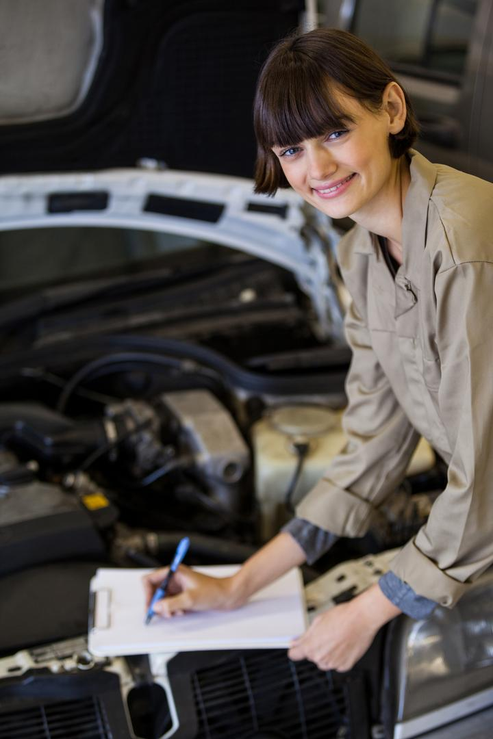 Female mechanic preparing a check list at the repair garage Free Stock Images from PikWizard