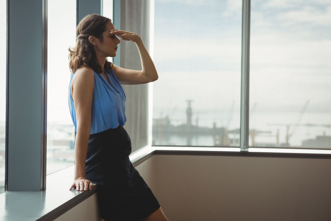 Tensed executive standing near window in office Free Stock Images from PikWizard
