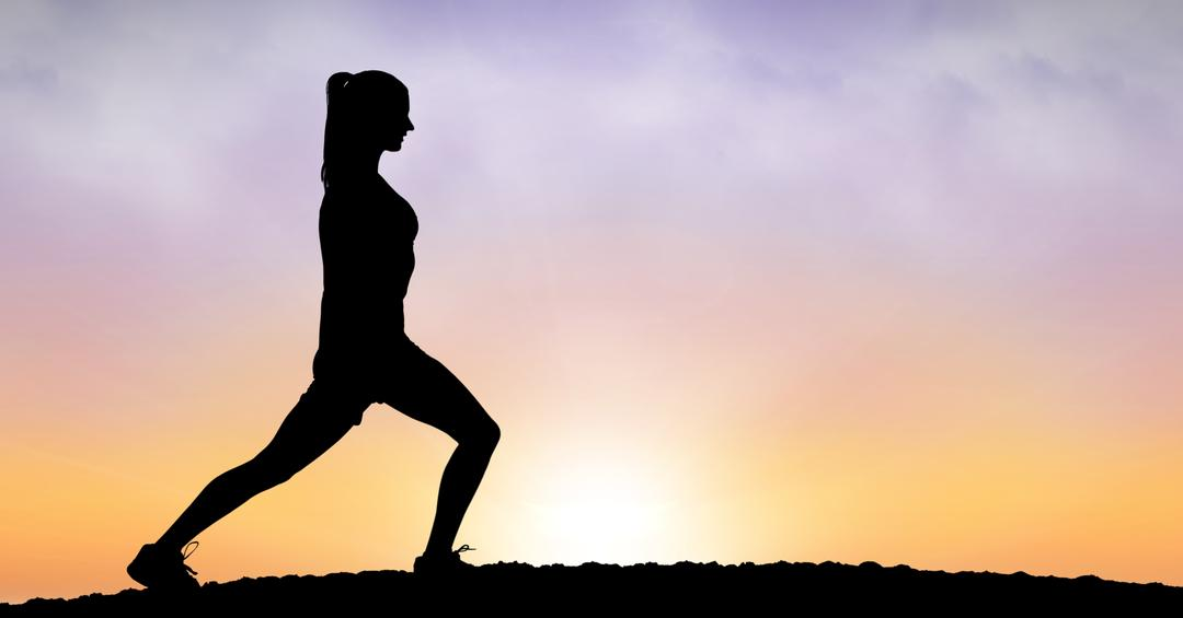 Image of a Silhouette of a Woman Streching at Sunset
