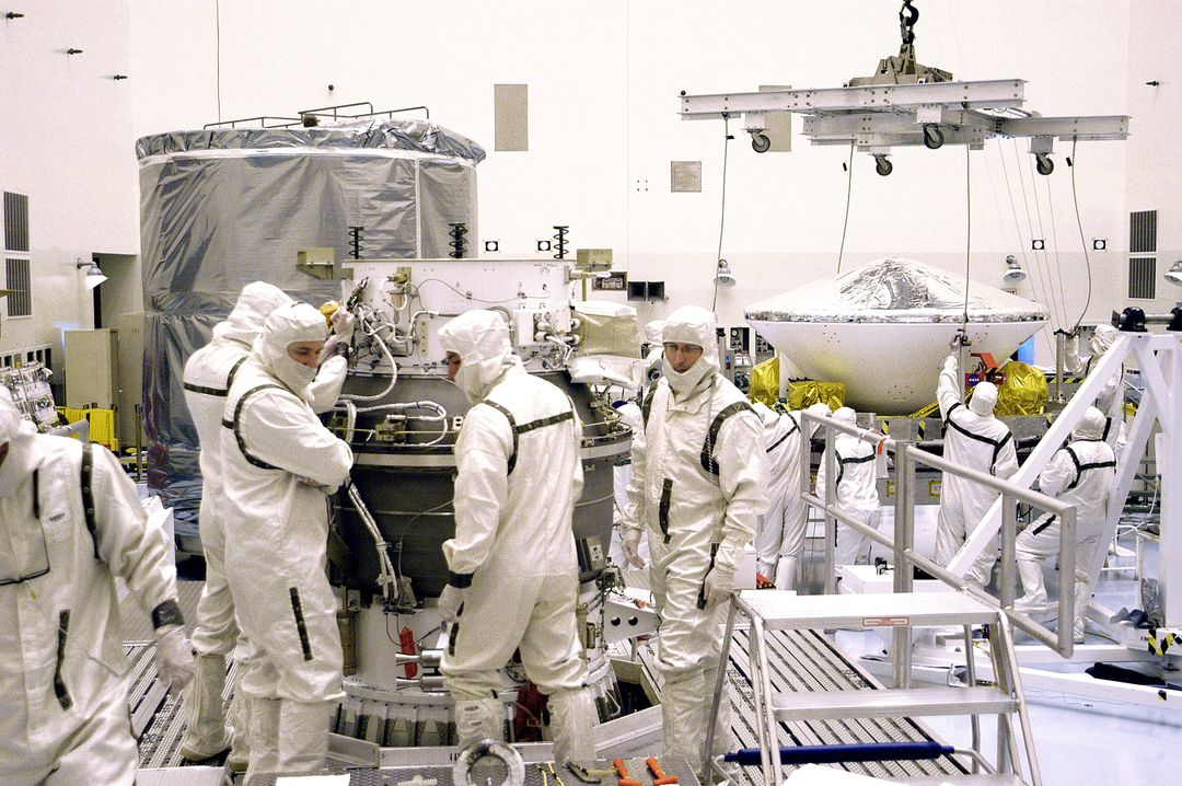 KENNEDY SPACE CENTER, FLA. - In the background, right, workers in the Payload Hazardous Servicing Facility get ready to lift Mars Exploration Rover 1 (MER-B) to the third stage of the Delta rocket (foreground) for mating.  The second of twin rovers being sent to Mars, it is equipped with a robotic arm, a drilling tool, three spectrometers, and four pairs of cameras that allow it to have a human-like, 3D view of the terrain. Each rover could travel as far as 100 meters in one day to act as Mars scientists' eyes and hands, exploring an environment where humans can't yet go.  MER-B is scheduled to launch from Launch Pad 17-B, Cape Canaveral Air Force Station, June 26 at one of two available times,  12:27:31 a.m. EDT or 1:08:45 a.m. EDT.