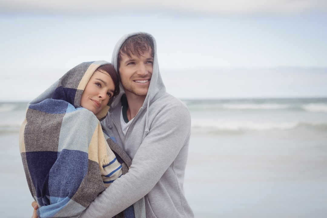 Thoughtful youn couple embracing at beach during winter Free Stock Images from PikWizard