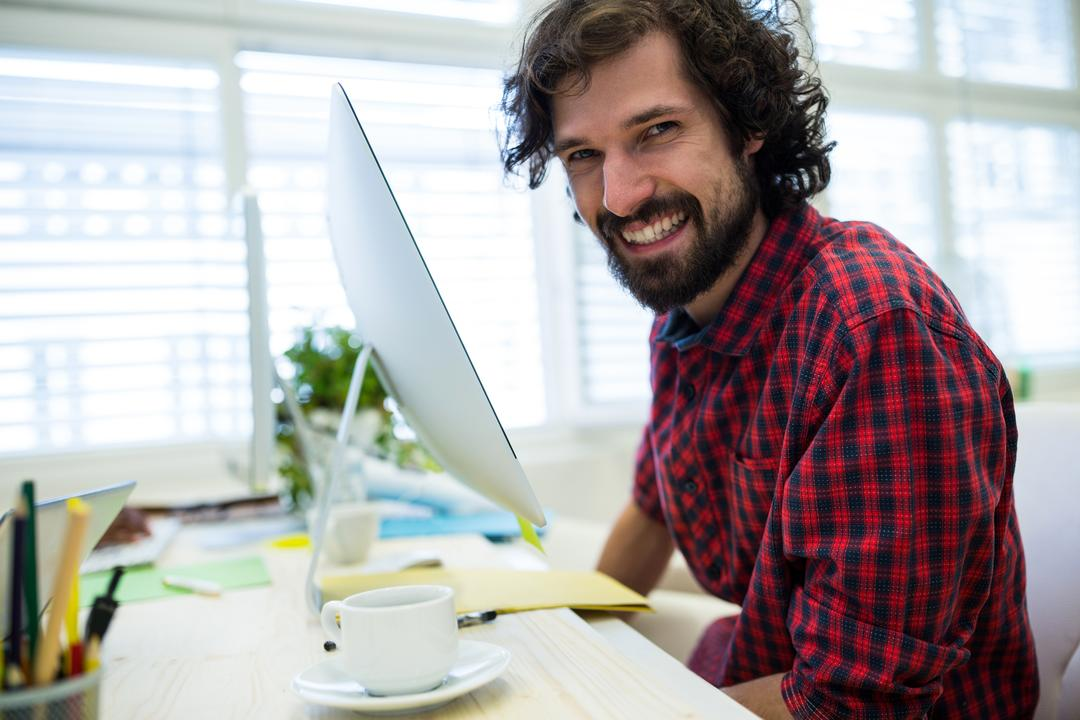 Male graphic designer smiling while working in office