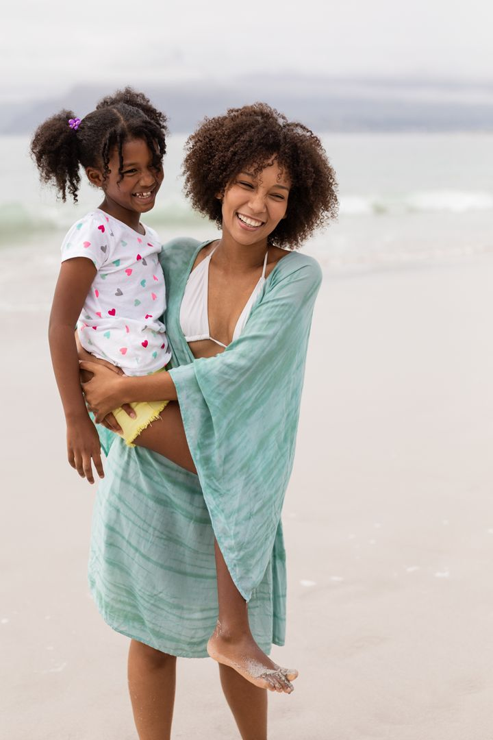 Front view of happy African American mother and daughter standing together at beach on a sunny day