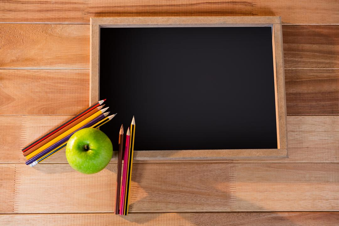 Close-up of chalkboard with colored pencil and apple on a table 4k