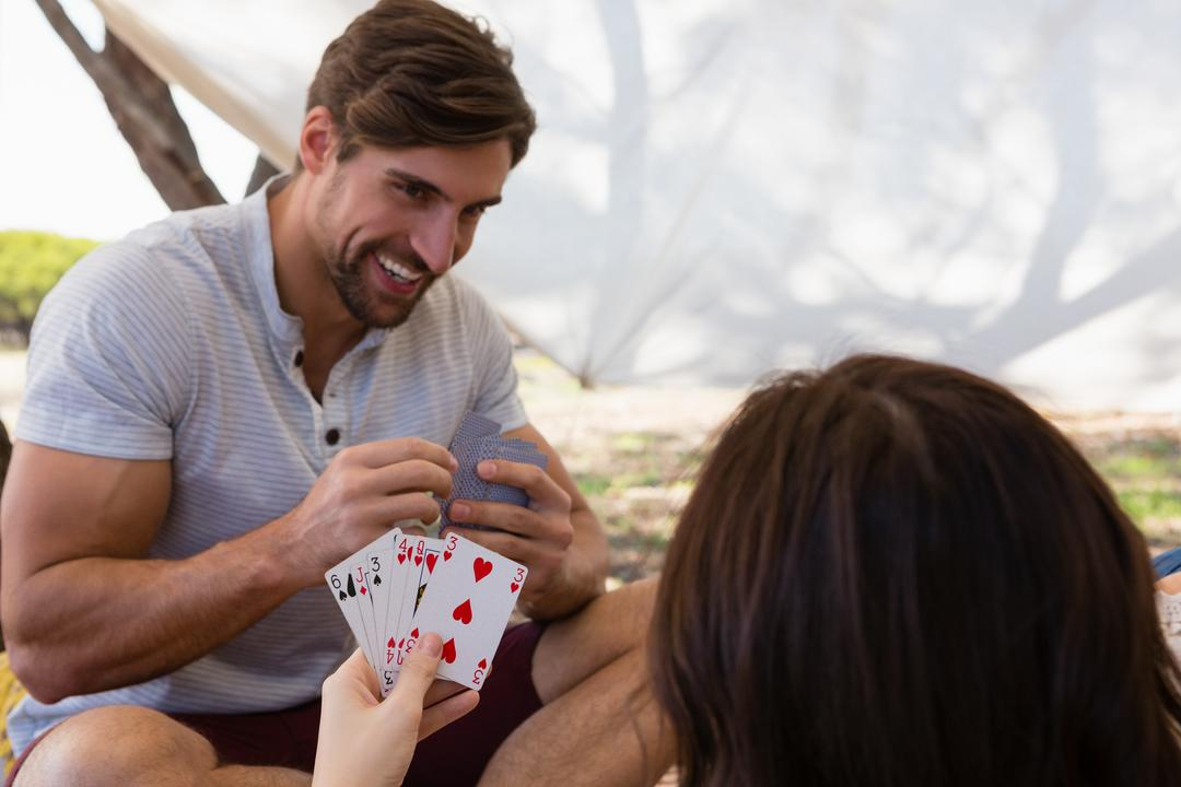 Smiling young man playing cards with woman in tent Free Stock Images from PikWizard