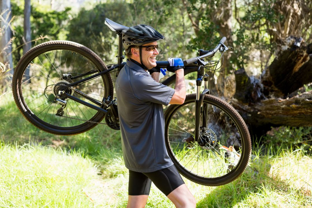 Man holding his mountain bike in forest