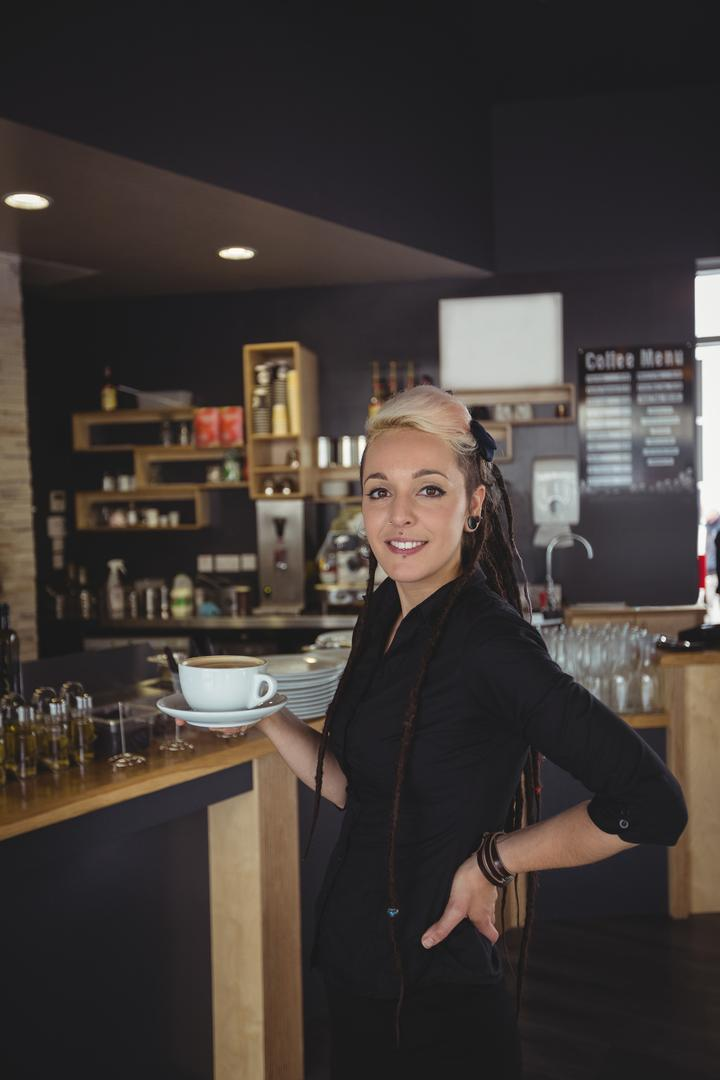 Portrait of waitress standing with cup of coffee in cafe