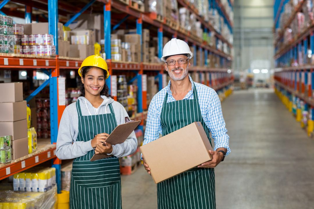 Portrait of warehouse workers standing with clipboard and cardboard boxes in warehouse Free Stock Images from PikWizard
