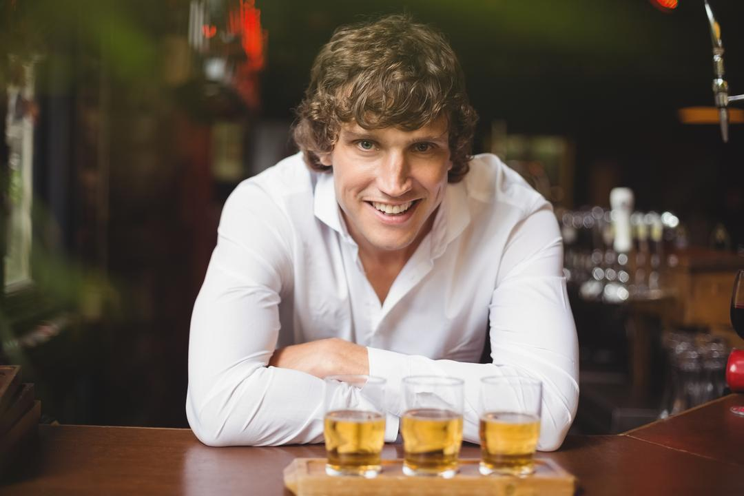 Portrait of bartender with tray of whisky shot glasses at bar counter in bar
