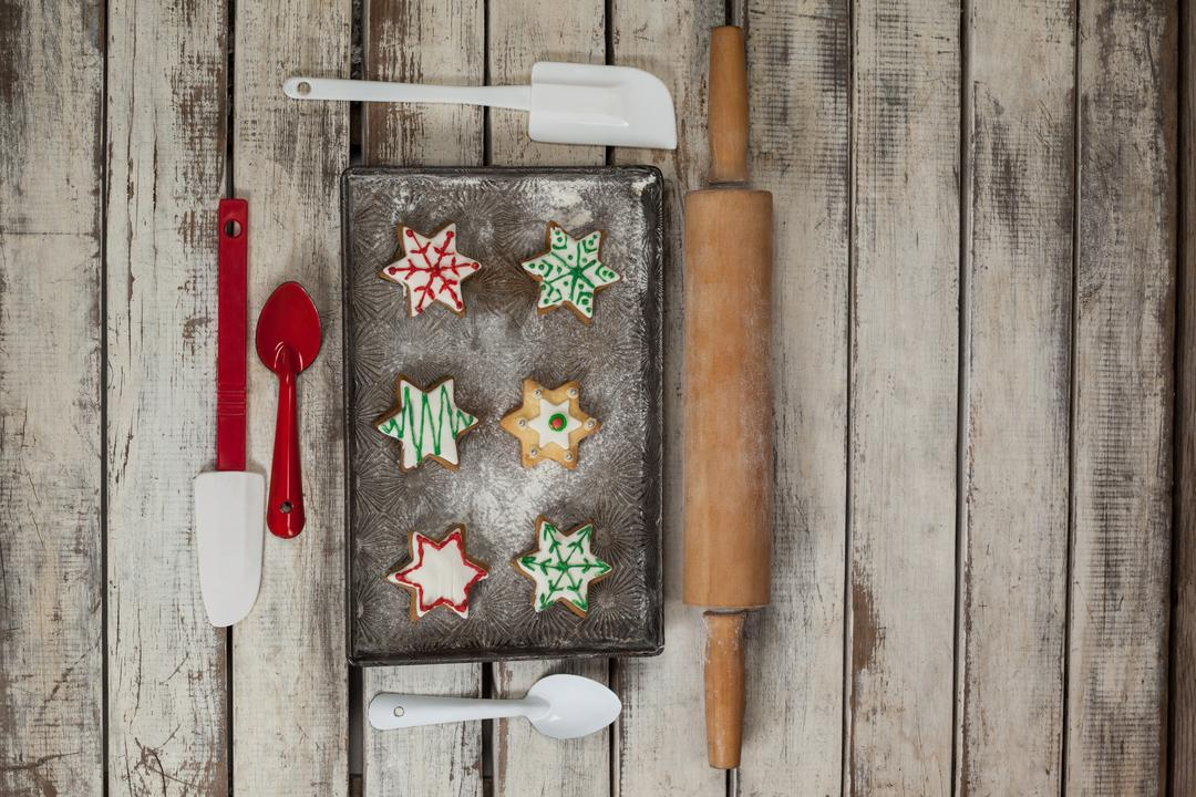 Spatula, spoon, rolling pin and tray with baked Christmas cookies kept on wooden table