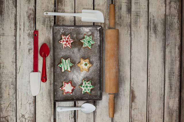 Spatula, spoon, rolling pin and tray with baked Christmas cookies
