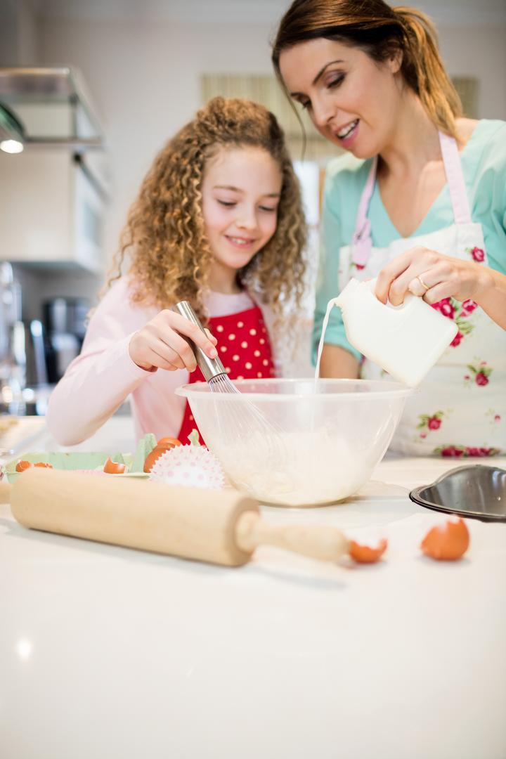 Mother assisting daughter in whisking flour in kitchen