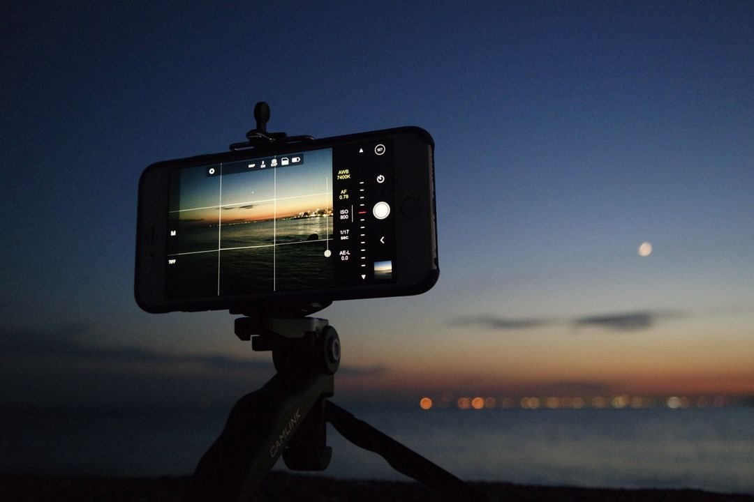 smartphone with camera on, placed on a tripod, pointing towards a beautiful sunset