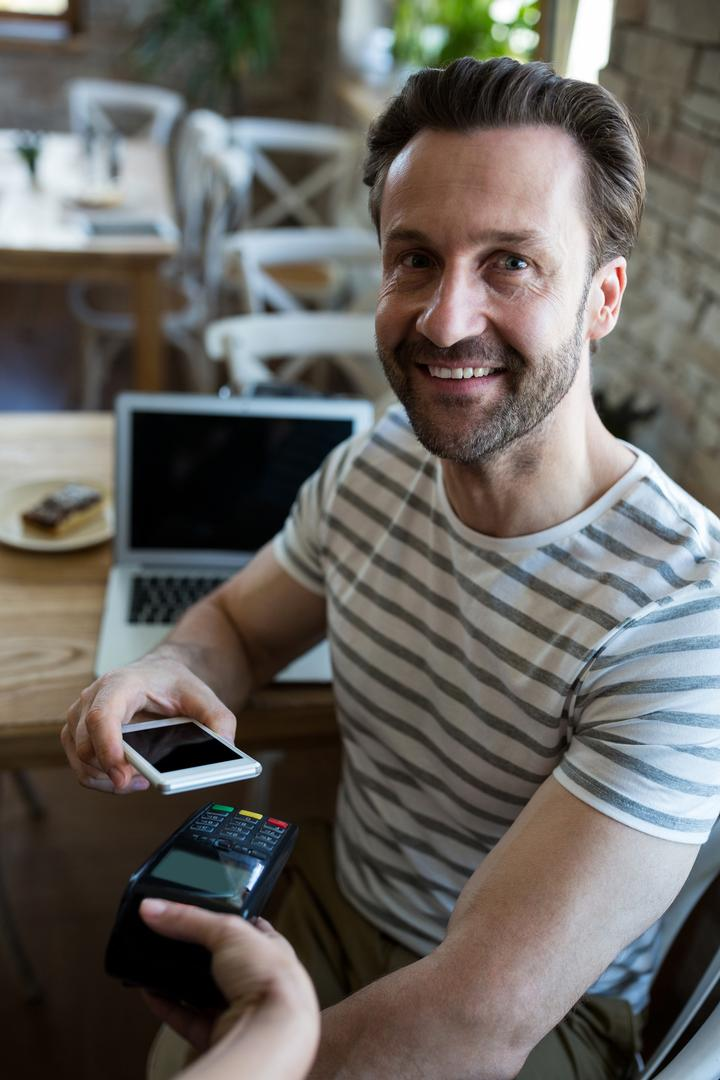 Portrait of smiling man sitting in coffee shop and paying with NFC technology on mobile phone