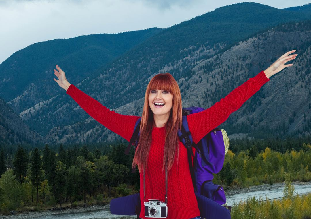Digital composite of mountain travel, happy red hair woman with camera and red jumper in front of the river in the mounta