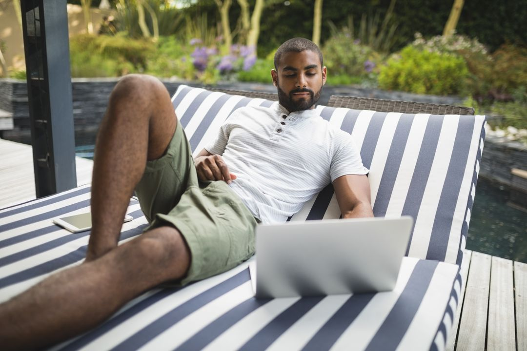 Man using laptop while relaxing on lounge chair at porch Free Stock Images from PikWizard