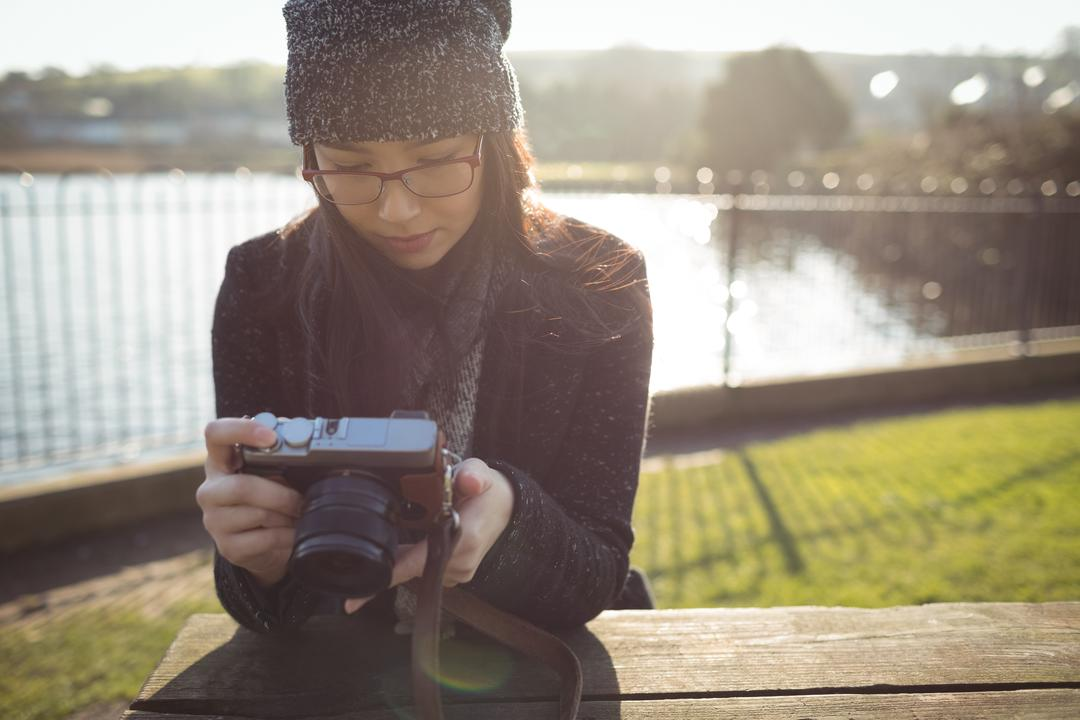 Woman looking at photos on digital camera on a sunny day Free Stock Images from PikWizard