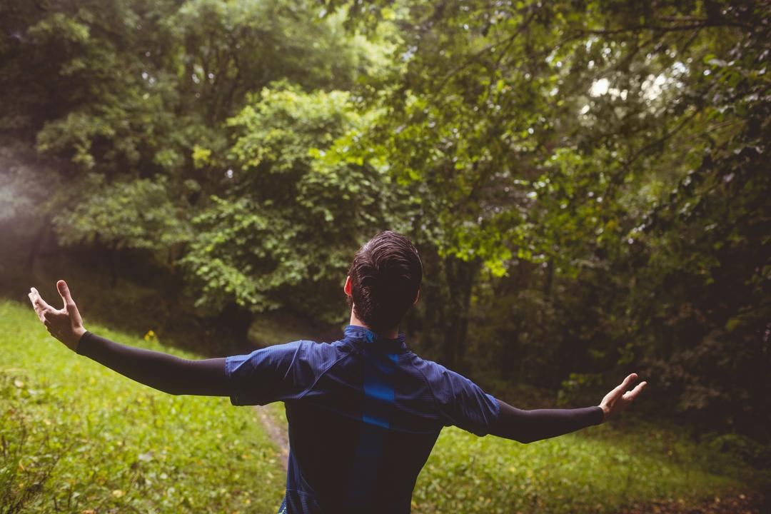 Excited athlete with his arms outstretched in forest