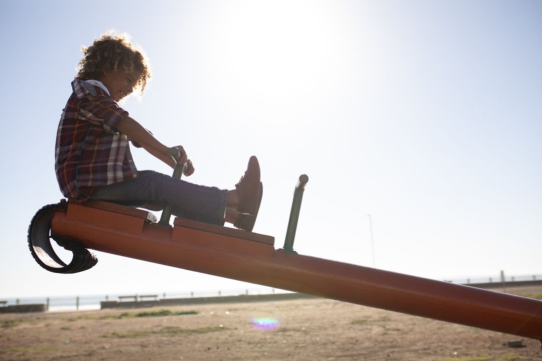 Side view of a mixed race boy enjoying time playing at a playground, sitting on a see-saw on a sunny day by the sea Free Stock Images from PikWizard