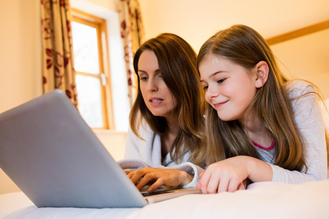 Mother and daughter using laptop in bedroom at home