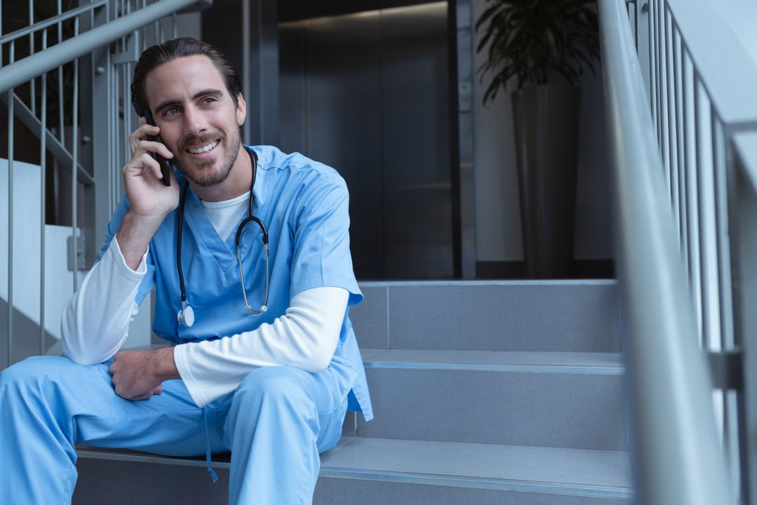 Front view of happy male surgeon talking on mobile phone while sitting on stairs at hospital