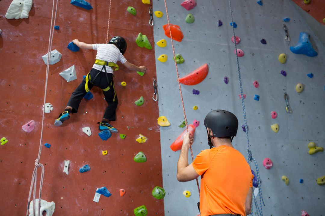 Trainer assisting boy in rock climbing at fitness studio Free Stock Images from PikWizard