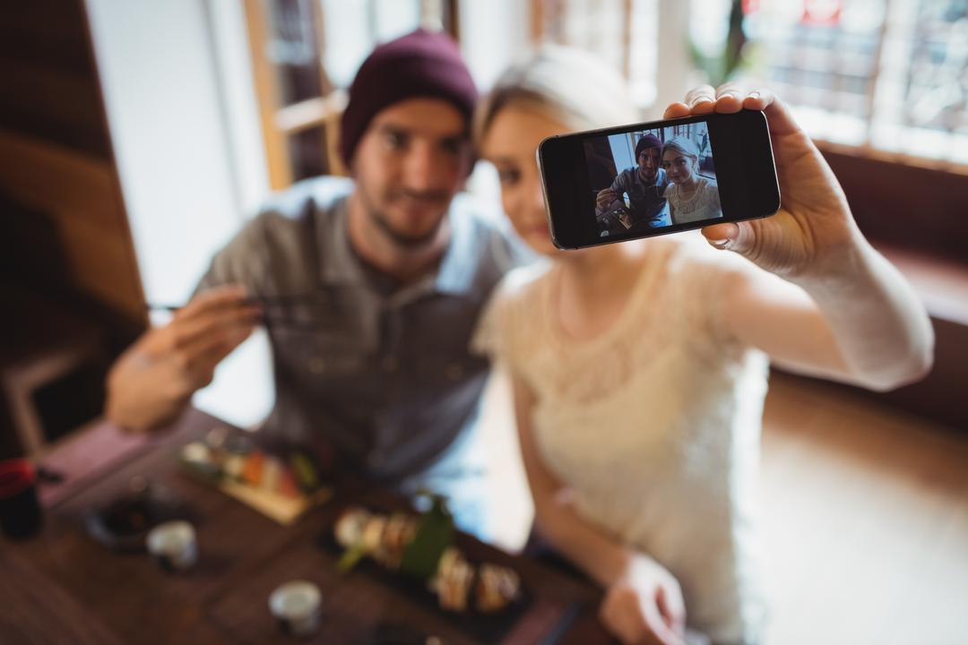 Couple taking selfie while having sushi in restaurant