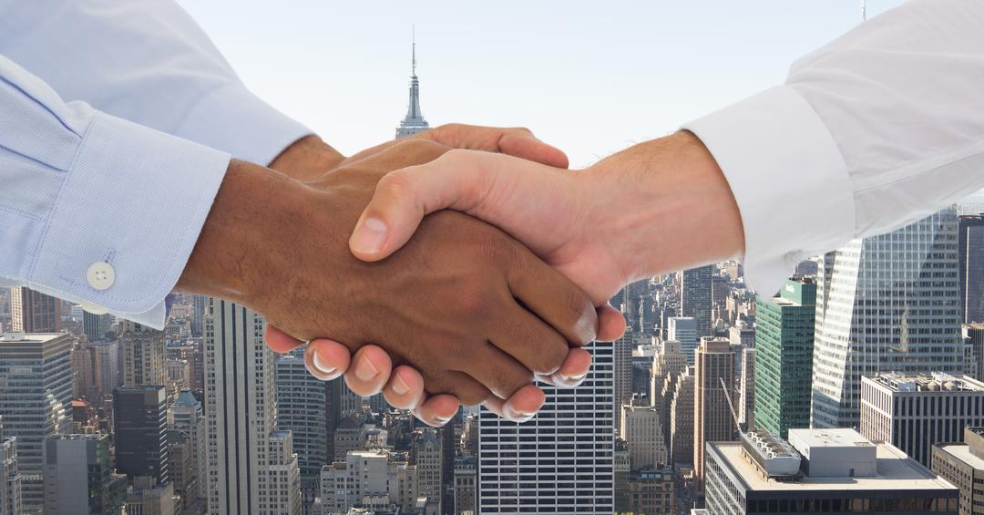 Cropped image of business people doing handshake against city