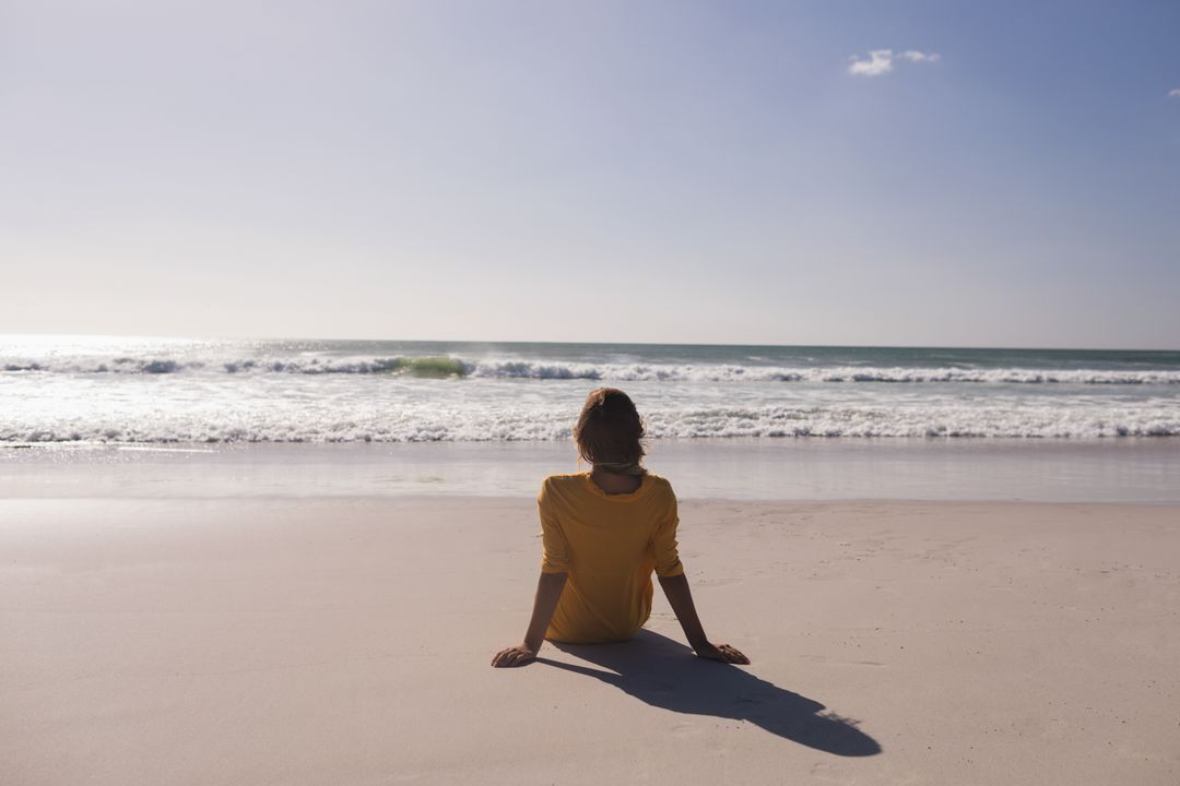 Rear view of woman relaxing and looking at view on the beach Free Stock Images from PikWizard