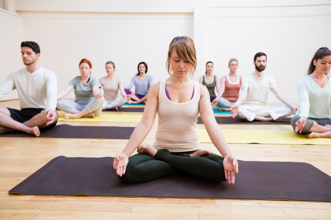 Trainer assisting group of people with lotus position in the fitness studio Free Stock Images from PikWizard