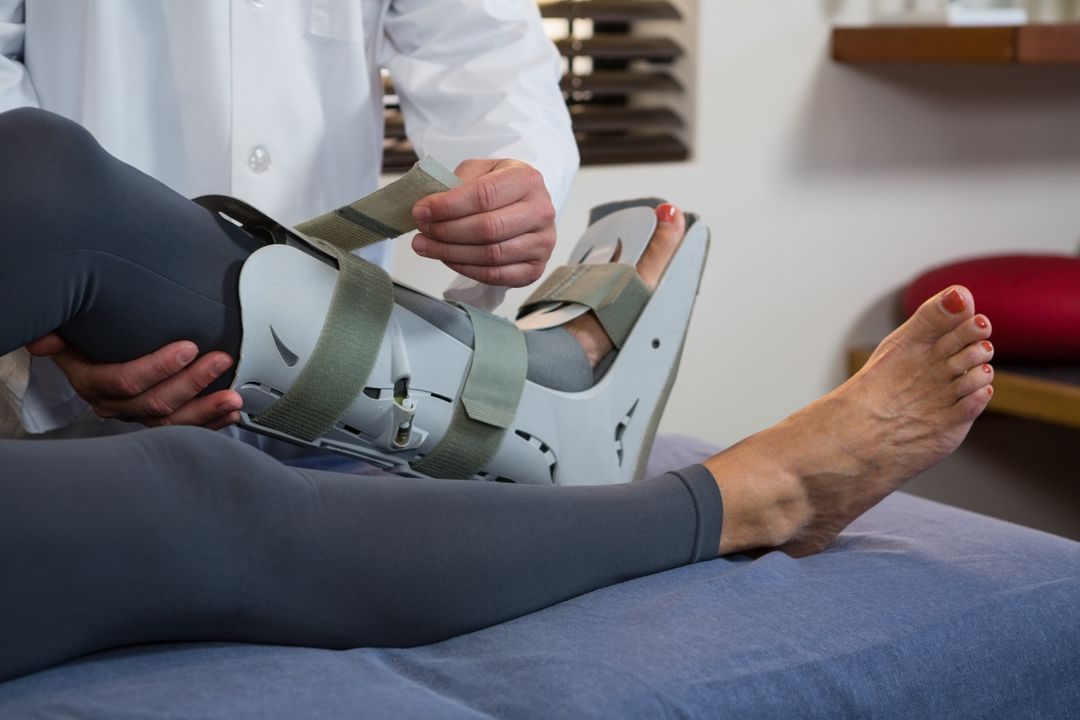 Physiotherapist tying leg pad in clinic Free Stock Images from PikWizard