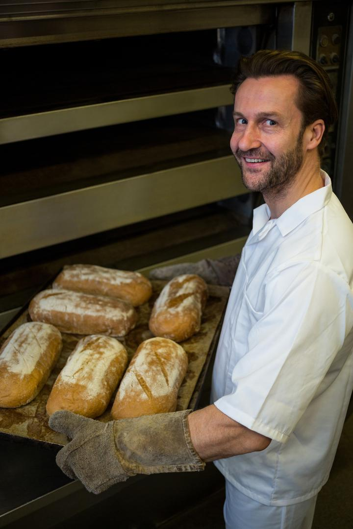 Portrait of smiling baker carrying a tray of baked buns Free Stock Images from PikWizard