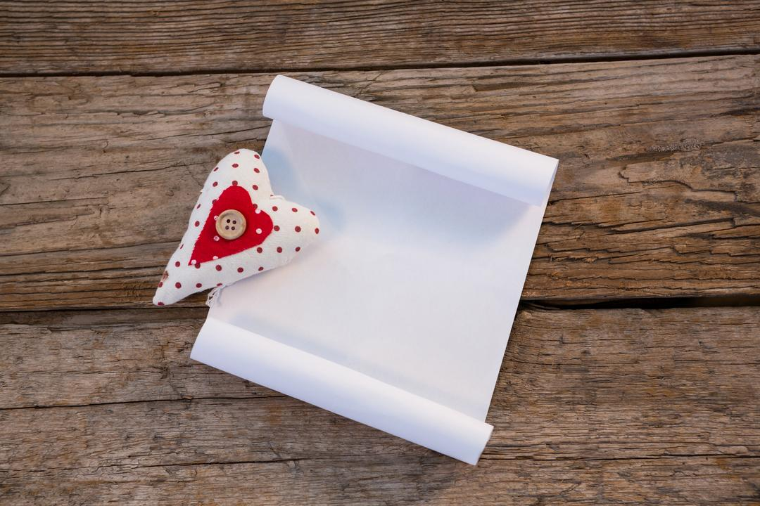 Heart and blank paper on wooden plank during christmas time