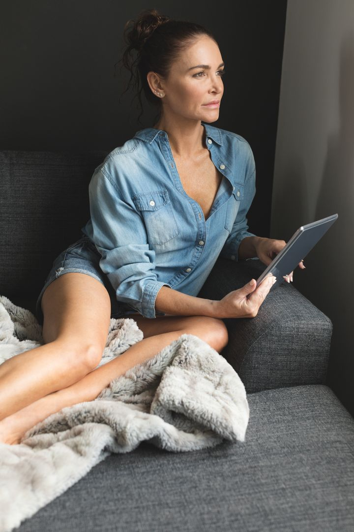 Front view of woman looking away while using digital tablet on sofa in a comfortable home