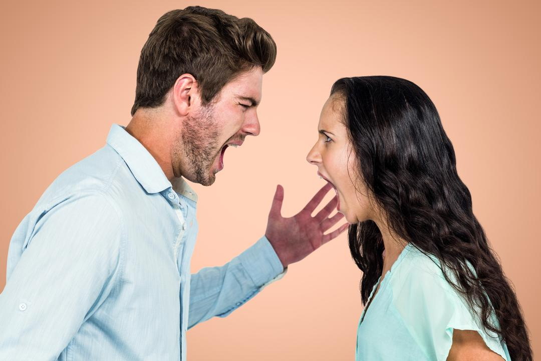 Side view of angry couple fighting against orange background