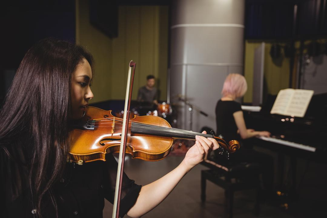 Two female students playing violin and piano in a studio